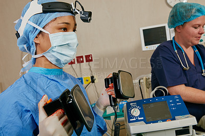Buy stock photo Shot of a surgeon using a defibrillator on a patient during surgery