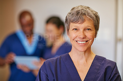 Buy stock photo Cropped portrait of a female doctor standing in a hospital with her colleagues in the background