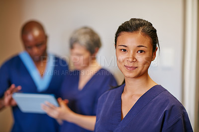 Buy stock photo Cropped portrait of a female nurse standing in a hospital with her colleagues in the background