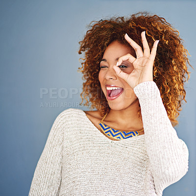 Buy stock photo Studio shot of a young woman looking through her fingers against a grey background