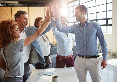 Buy stock photo Cropped shot of a group of businesspeople high fiving in the office
