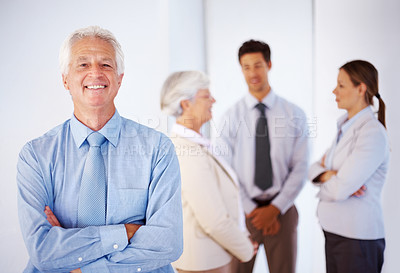 Buy stock photo Portrait of cheerful senior businessman standing with his hands folded with colleagues discussing in background