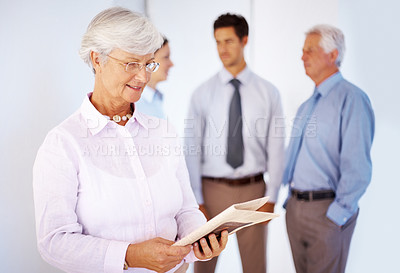 Buy stock photo Senior woman reading newspaper with people standing in background discussing