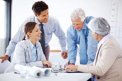 Buy stock photo Team of smiling professionals discussing plan in a conference room