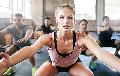 Buy stock photo Shot of a group of people doing squats in a gym