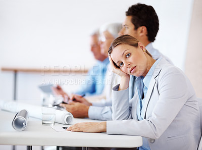 Buy stock photo Young businesswoman bored at a conference with her colleagues