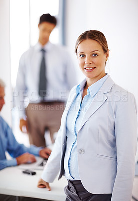 Buy stock photo Portrait of a confident young businesswoman standing in office with her colleagues at the back