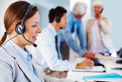 Buy stock photo Female call center executive working at her desk with colleagues in background
