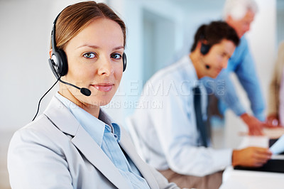 Buy stock photo Beautiful female call center executive sitting at her desk with colleagues in background