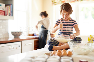 Buy stock photo Shot of a little girl helping her mom bake in the kitchen
