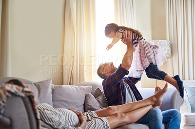 Buy stock photo Shot of a father playing with his daughter while her pregnant mother relaxes with them on the sofa