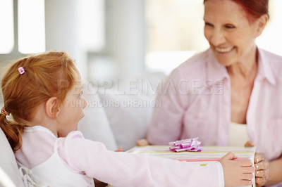 Buy stock photo Portrait of a mature woman giving a present to her surprised granddaughter