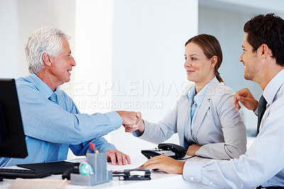 Buy stock photo Portrait of a smart young couple shaking hands and making a deal with a agent at office