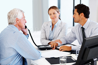 Buy stock photo Portrait of a financial advisor using telephone during a meeting with a young couple at office