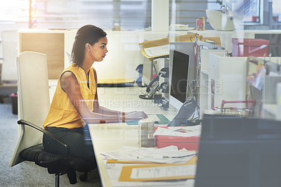 Buy stock photo Shot of a young woman working on a computer in an office