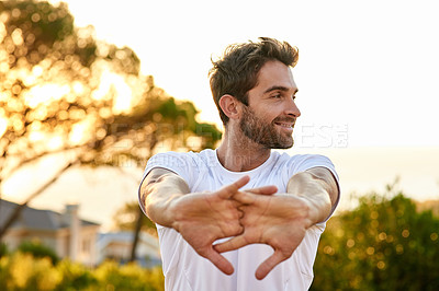Buy stock photo Shot of a man stretching before a run