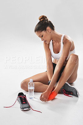 Buy stock photo Cropped shot of a young woman holding her injured foot that's highlighted in red