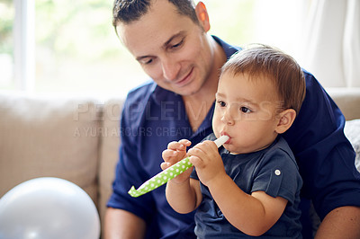 Buy stock photo Shot of a father and son playing with a party horn on his first birthday