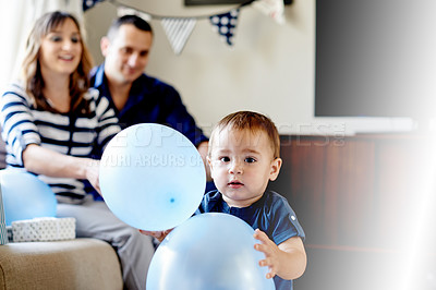 Buy stock photo Portrait of an adorable little boy playing with balloons on his first birthday at home