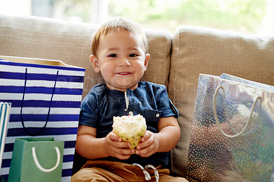 Buy stock photo Shot of an adorable little boy sitting on the sofa with a cupcake on his first birthday at home