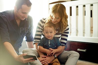 Buy stock photo Shot of a happy family showing their adorable son something on their phone