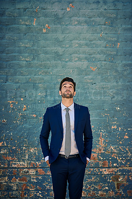 Buy stock photo Shot of a young corporate businessman standing against a brick wall