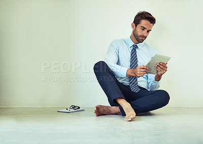 Buy stock photo Shot of a young corporate businessman sitting on the ground with a digital tablet