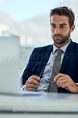 Buy stock photo Shot of a young corporate businessman sitting at a desk in front of a laptop