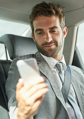 Buy stock photo Cropped shot of a handsome young businessman using on a cellphone in the back seat of a car