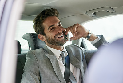 Buy stock photo Cropped shot of a handsome young businessman talking on a cellphone in the back seat of a car