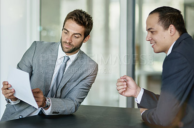 Buy stock photo Shot of two colleagues looking over paperwork together in an office