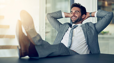 Buy stock photo Shot of a businessman leaning back in his chair with his feet on a desk and hands behind his head