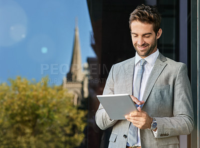 Buy stock photo Shot of a handsome young businessman using a digital tablet outside
