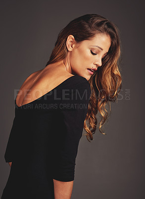 Buy stock photo Studio shot of a beautiful woman with long locks posing against a grey background