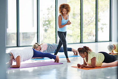 Buy stock photo Shot of a group of women doing yoga indoors