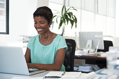 Buy stock photo Shot of an ambitious woman using a laptop at her desk in a modern office