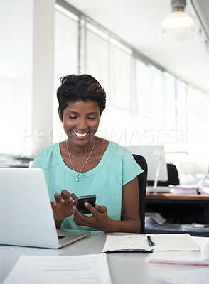 Buy stock photo Shot of an ambitious woman using a phone at her desk in a modern office