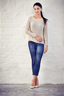 Buy stock photo Shot of a casually dressed young woman standing against a brick wall