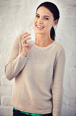 Buy stock photo Portrait of a young woman drinking a glass of milk