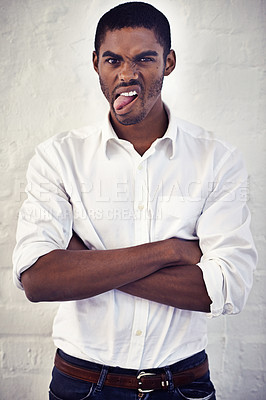 Buy stock photo Portrait of a young man with his arms crossed sticking out his tongue