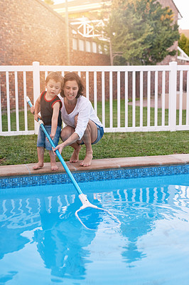 Buy stock photo Shot of a mother and son cleaning the pool together