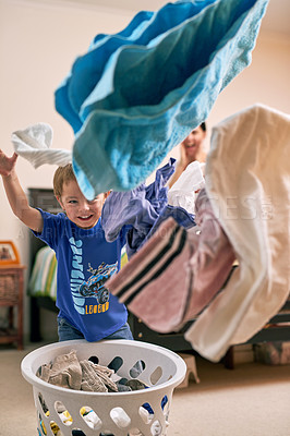 Buy stock photo Portrait of a little boy throwing laundry in the air