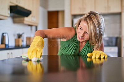 Buy stock photo Shot of a young woman cleaning a kitchen surface