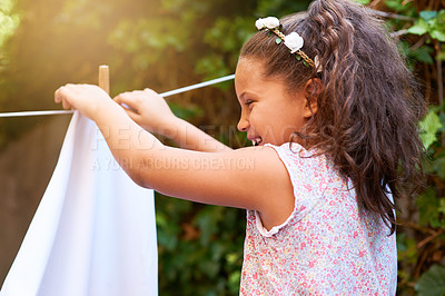 Buy stock photo Shot of a young girl hanging up laundry on a washing line