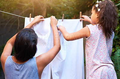 Buy stock photo Shot of a mother and daughter hanging up laundry on a washing line