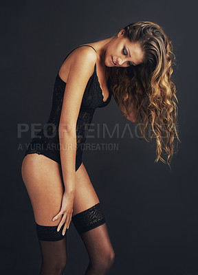 Buy stock photo Shot of an attractive young woman posing in a black bodysuit against a black background