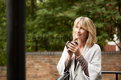 Buy stock photo Shot of a mature woman sitting on her balcony drinking coffee