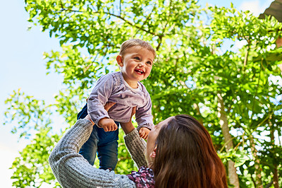 Buy stock photo Shot of a mother holding her smiling baby girl up in the air outdoors