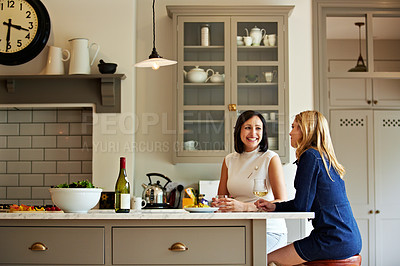 Buy stock photo Shot of a two friends talking and drinking wine in a kitchen