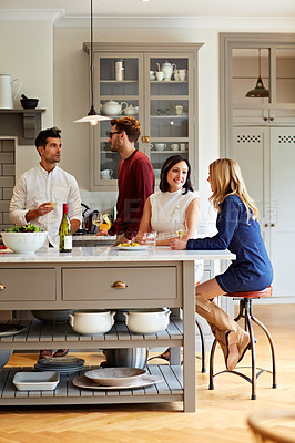 Buy stock photo Shot of a group of friends talking and drinking wine together while preparing dinner